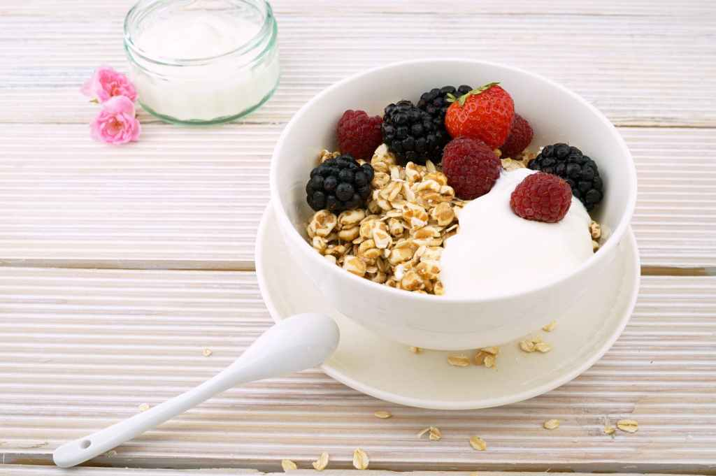 yogurt topped with seeds and granola and placed in a small white and blue floral bowl